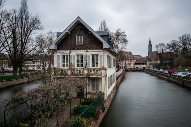 Canal surrounded by buildings and greenery under a cloudy sky in strasbourg in france