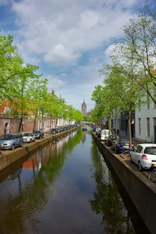 Canal waters and old church  tower of delft, holland