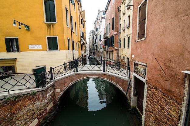 Канал с гондолами в венеции, италия. архитектура и достопримечательности венеции. открытка венеции с гондолами венеции.