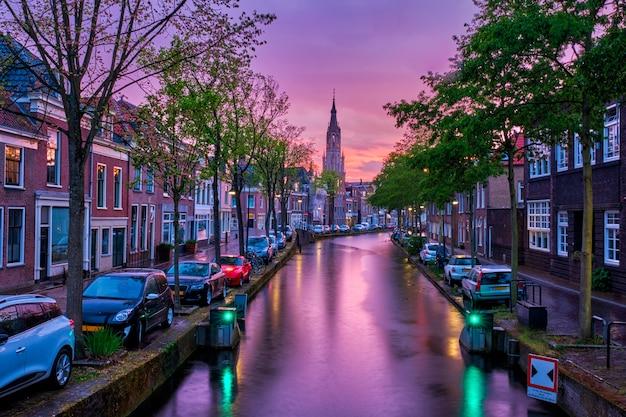 Канал с припаркованными вдоль автомобилей в дельфте, нидерланды