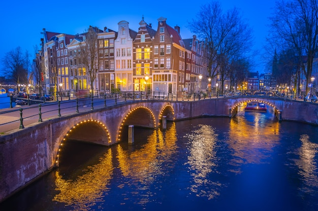 Canals of amsterdam with dutch buildings at night in amsterdam city, netherlands