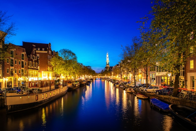 Каналы амстердама ночью в нидерландах. амстердам - столица и самый густонаселенный город нидерландов.
