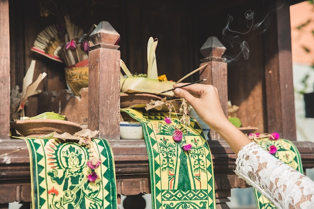 Canang sari with incense on temple