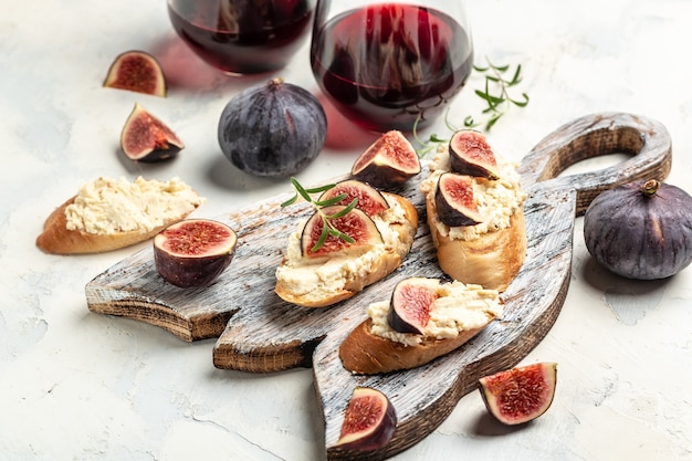 Canape or crostini with toasted baguette, fresh figs, cream cheese and red wine. delicious appetizer, ideal aperitif. top view.