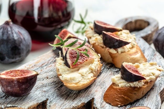 Canape or crostini with toasted baguette, fresh figs, cream cheese and red wine. delicious appetizer, ideal aperitif. top view