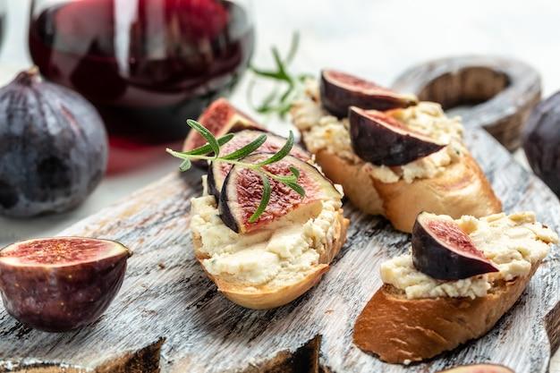 Канапе или кростини с поджаренным багетом, свежим инжиром, сливочным сыром и красным вином. вкусная закуска, идеальный аперитив. вид сверху