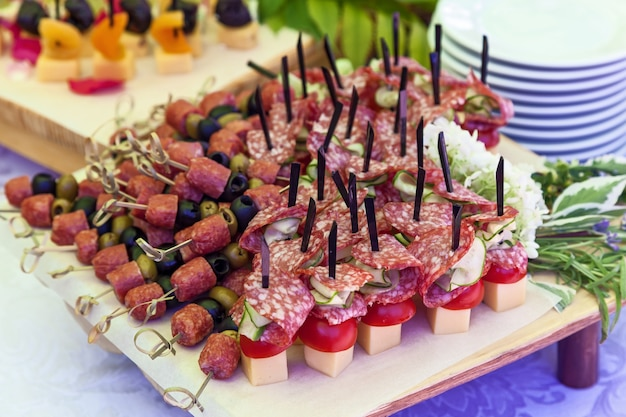 Canape on skewers with salami and olives salami tomato and cheese on a buffet for a party