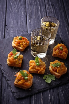 Canape with eggplant caviar and glasses of wine. selective focus