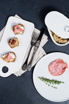 Canape with ham, salami and duck pate on a white cutting board&