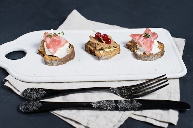 Canape with ham, salami and duck pate on a white cutting board