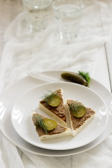 Canape with pate, canned cucumber and dill. snack.