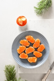 Canape with red caviar for new year or christmas party on white table. vertical format.
