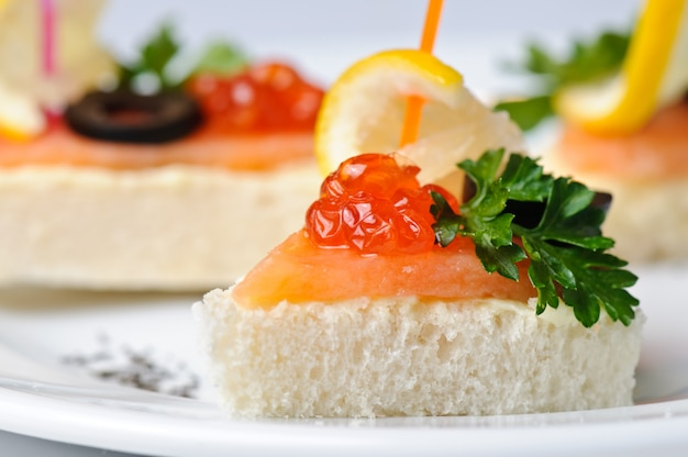 Canape with red caviar and smoked salmon, served on plate