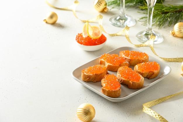 새 해 또는 흰색 바탕에 크리스마스 파티를위한 레드 연어 캐 비어와 canape. 축제 휴일 저녁. 맛있는 아 페타이 저와 샴페인. 공간을 복사하십시오.