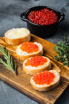 Canape with red salmon caviar, for new year, on gray table