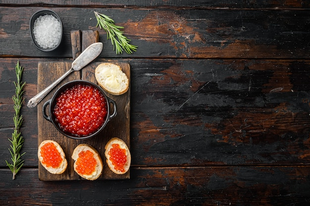 Canape with red salmon caviar for new year, on old dark wooden table