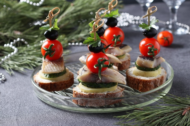 Canape with salted herring, cucumber, boiled potatoes, cherry tomato and black olives on rye croutons on gray background. closeup