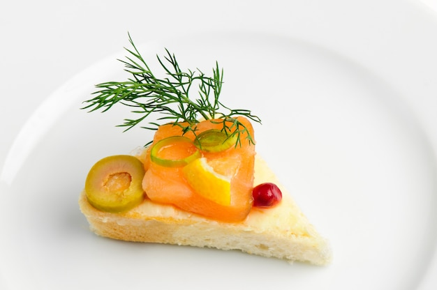 Canape with slice of smoked salmon, green olive, dill and seed of pomegranate