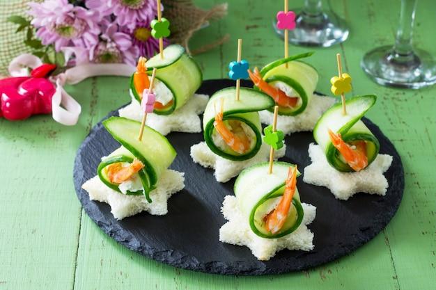 축제 테이블에 흰 빵, 오이, 리 코타 및 왕 새우와 canape. 발렌타인 데이 개념 또는 결혼식.