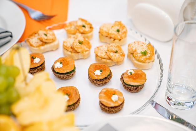 カナッペ。便利なビュッフェフィード。お祭りで小さなサンドイッチ。ケータリング。調理済みの食事の配達と宴会のサービス。