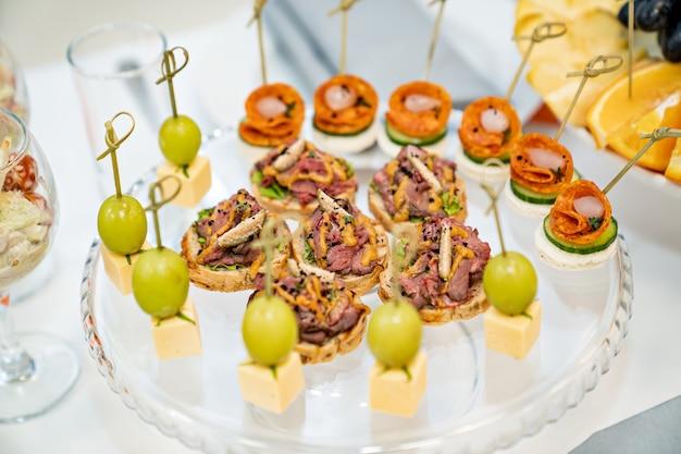 카나페. 편리한 뷔페 피드. 축제에서 작은 샌드위치. 케이터링. 준비된 식사 배달 및 연회 서비스.
