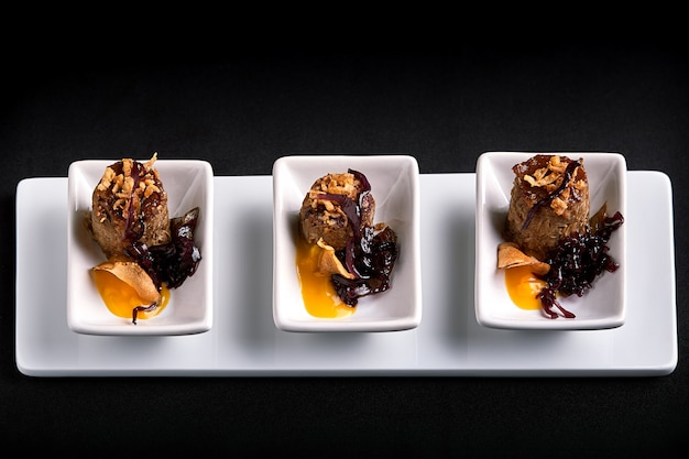 Canapes beef rolls with pumpkin sauce, on white plates