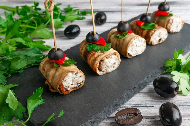 Canapes of fried eggplant stuffed with cheese, herbs. garnished with sweet pepper, parsley and olive. on a black slate board. gray background. close-up.
