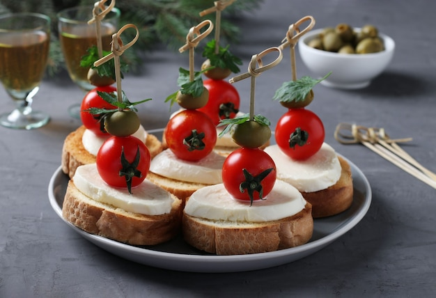 Canapes of mozzarella, cherry tomatoes, green olives, parsley on croutons of white bread on dark gray background