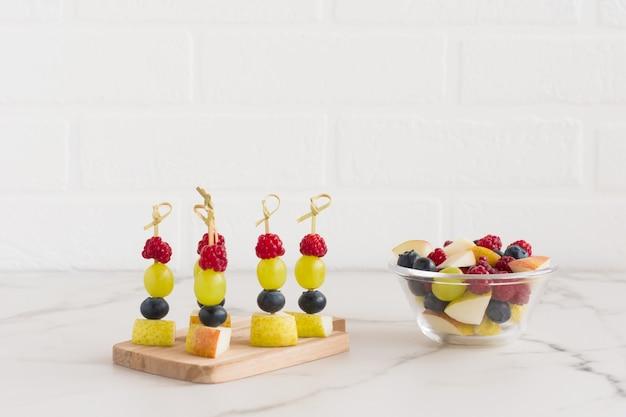 Канапе из сочных фруктов на деревянной доске и миска с нарезанными фруктами банан, груша, малина. вкусная, здоровая еда.