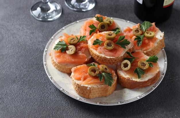 짙은 회색 배경에 흰 빵 크루통에 소금에 절인 연어, 녹색 올리브, 파슬리 카나페. 축제 간식. 확대