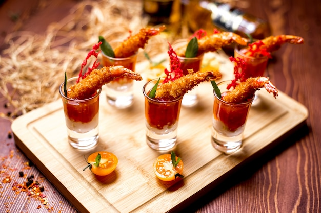 Canapes in shots with fried prawns in tomato sauce side view