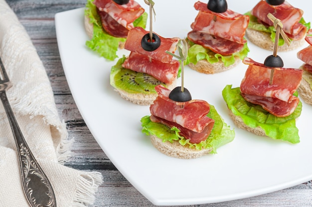 Canapes with carbonade, kiwi and lettuce on a white wheat bread. garnished with olive. on a white plate. near a fork and a napkin.