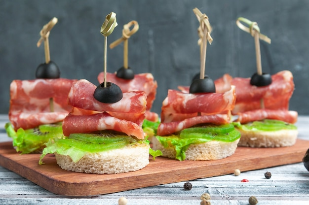 Canapes with carbonade, kiwi and lettuce on a white wheat bread. garnished with olive. on a wooden board. close-up.