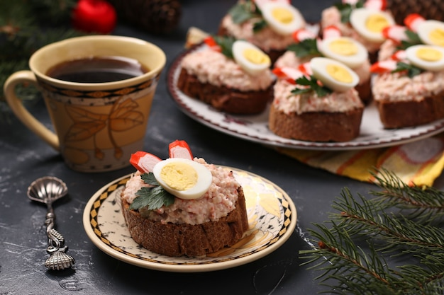 暗い背景にクリームチーズ、豆、カニカマ、ウズラの卵、コーヒーのカナッペ。閉じる