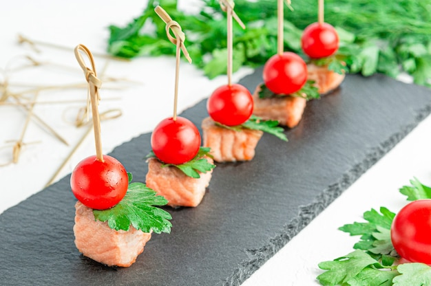 Canapes with fried trout, cherry tomatoes and parsley. on a dark slate board. close-up. isolated. white background