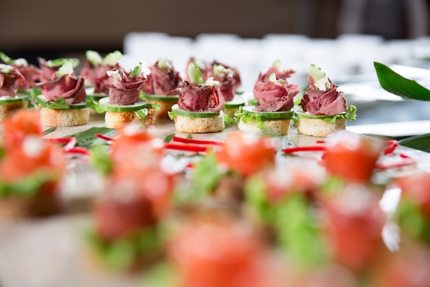 Canapes with meat and cucumber on buffet table