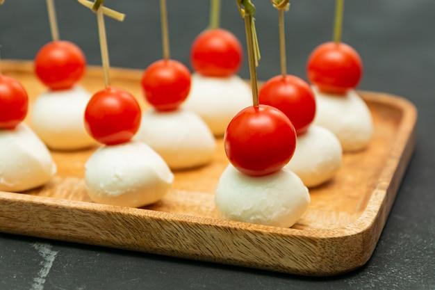 Канапе с сыром моцарелла и помидорами черри подается на деревянном подносе