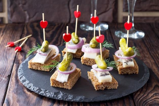 축제 테이블에 호밀 빵, 청어 및 피클을 곁들인 카나페. 발렌타인 데이 개념 또는 결혼식.