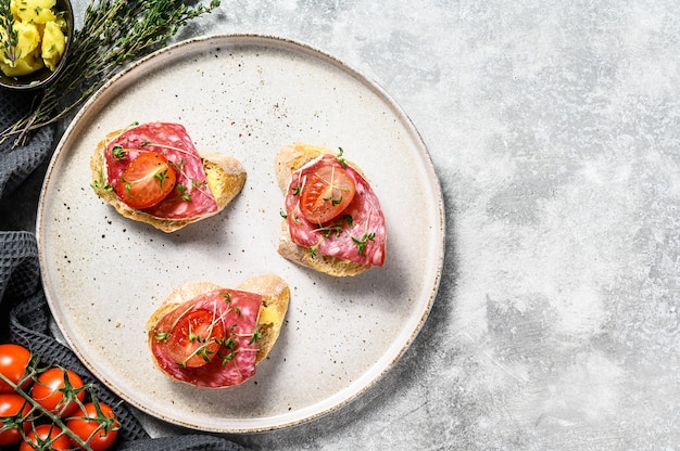 Canapes with salami salchichon, cherry tomatoes and micro greens on a baguette. gray background