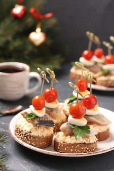 Canapes with salted herring, cheese, quail eggs and cherry tomatoes on rye croutons
