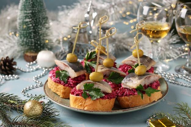 Канапе с соленой сельдью, оливками и свеклой на гренках из белого хлеба в тарелке на голубом фоне. горизонтальный формат. крупным планом