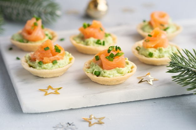 Canapes with smoked salmon, cream cheese and avocado on light background with space for text. christmas and new year holidays background concept.