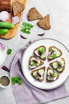 해바라기와 아마씨, 페타 치즈, 오이, 양파를 곁들인 구운 빵을 곁들인 카나페
