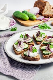 ヒマワリと亜麻の種子、フェタチーズ、キュウリ、タマネギのトーストしたパンのカナッペ