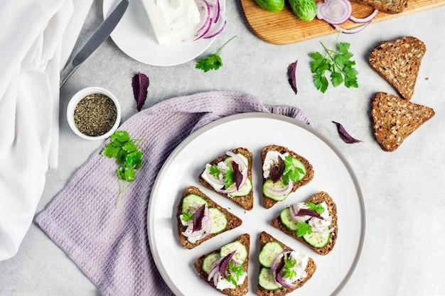 ひまわりと亜麻の種子のトーストしたパンのカナッペフェタチーズきゅうりと玉ねぎ