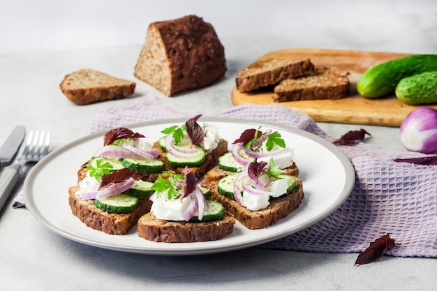 Canapes with toasted bread with sunflower and flax seeds, feta cheese, cucumber and onion
