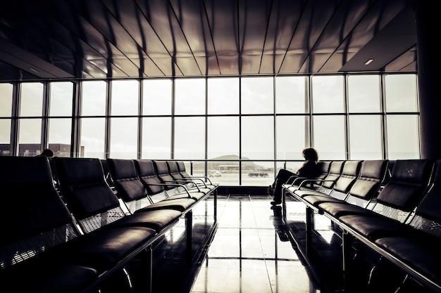 혼자 여행자가 좌석에 앉아 대기하는 공항 개념에서 지연 비행 취소-여행 및 게이트 시간-현대인 라이프 스타일-외로운 여행자 디지털 노매드