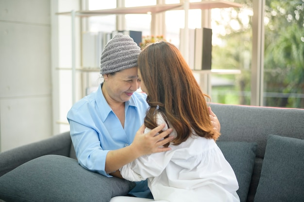 A cancer patient woman wearing head scarf hugging her supportive daughter indoors, health and insurance concept.