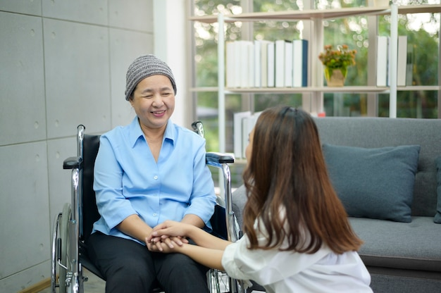 Cancer patient woman wearing head scarf sitting on wheelchair talking to her supportive daughter indoors, health and insurance concept.