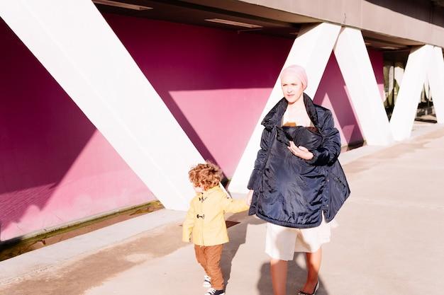 Больная раком женщина, пожимая руку своему трехлетнему сыну и несущая ребенка в платке, идет по улице с розовой стеной на заднем плане